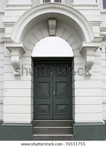 green door in a white arch - stock photo