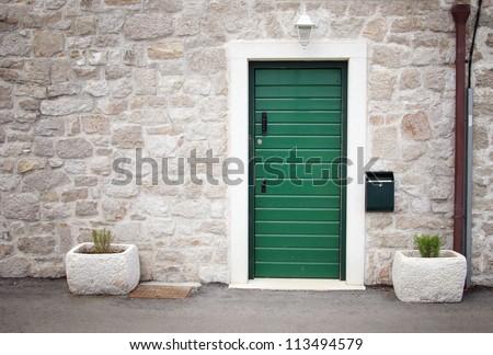 Green door in old stone house, Croatia - stock photo