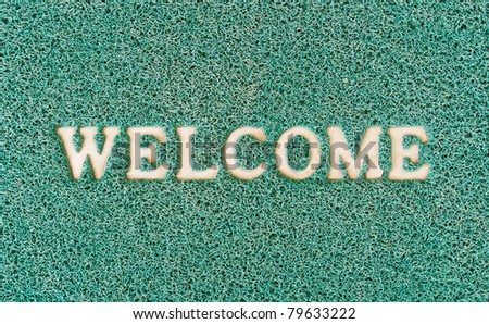 Green door mat with welcome written on it - stock photo