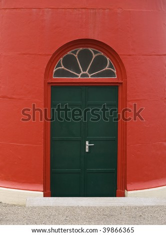 Green door of red lighthouse with window in the form of a flower