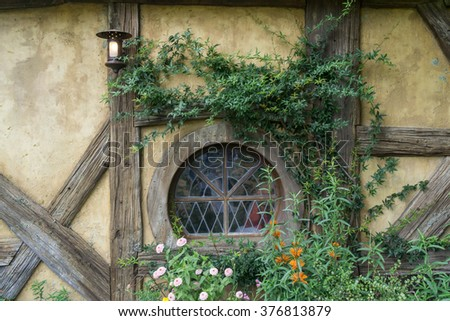 green dragon tavern wall with a small round window. Taken in hobbiton movie set in new zealand. - stock photo