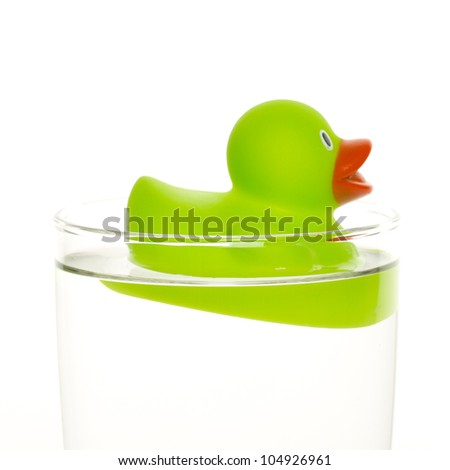 Green duck in a glass of water - stock photo
