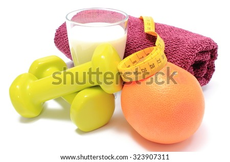 Green dumbbells and purple towel for using in fitness, fresh grapefruit, glass of milk and tape measure, concept for healthy nutrition and lifestyle. Isolated on white background - stock photo