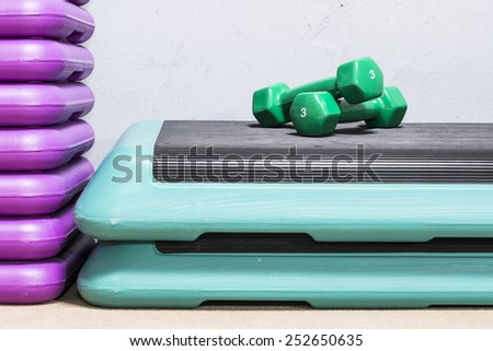 Green dumbbells on a step deck. Three kilograms. - stock photo