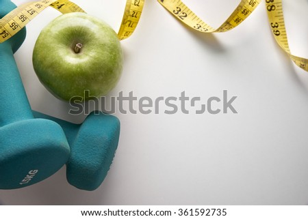 Green dumbbells with apple and tape measure. Concept health, diet and sports. Horizontal composition. Top view - stock photo
