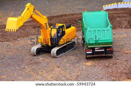 Green dumper and yellow excavator on a road building. Homemade RC model - plastic kit (  scratchbuild 1 : 32 scale) - stock photo