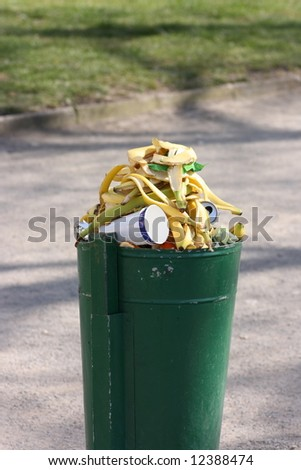 Green dust bin full of banana skins and other garbage - stock photo