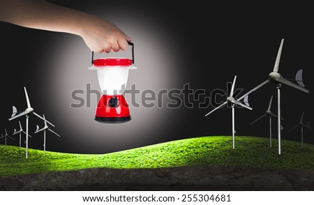 Green earth concept, eco power, wind turbines generating electricity and hand woman holding plastic electric lantern on black background, concepts of searching and direction - stock photo