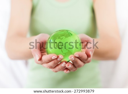 Green Earth Globe Protected by human hands. Glass globe in female hand.Sustainable development for the future of the our planet. - stock photo