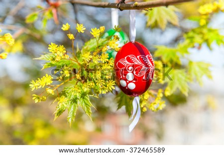Green Easter background with painted wooden eggs hanging from tree branches. This image is blurred, shallow DOF, focus on red egg. - stock photo