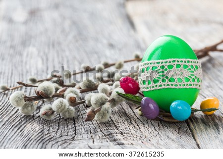 Green Easter egg decorated with lace and willow branch on wooden background. Selective focus, copy space  - stock photo