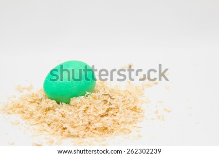 Green easter egg on sawdust with place for text - stock photo