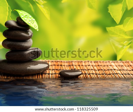 green eco background with spa stones and leaves with water and sunlight - stock photo