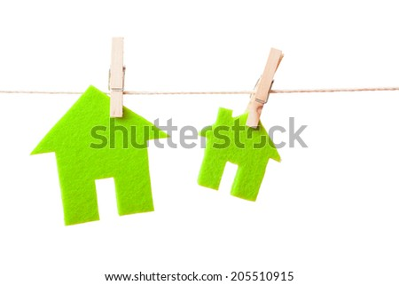 Green eco houses attach to rope with clothes pins on white background - stock photo
