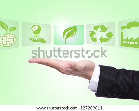 green eco icons concept , business man hand palm holding all kinds of icon about eco with green background - stock photo