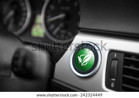 Green ECO mode button on a dashboard of a sportive car. - stock photo