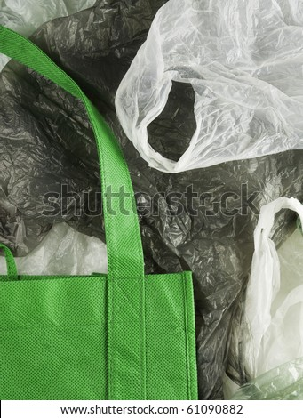 Green, eco shopping bag contrasting against disposable plastic bags. - stock photo