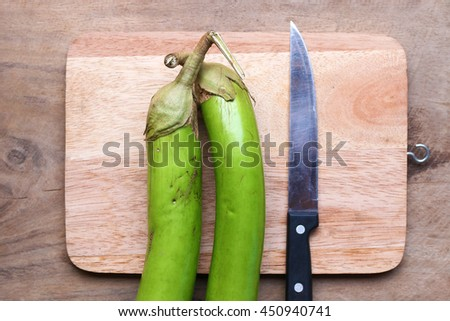 Green egg plant on a kitchen cutting board - stock photo