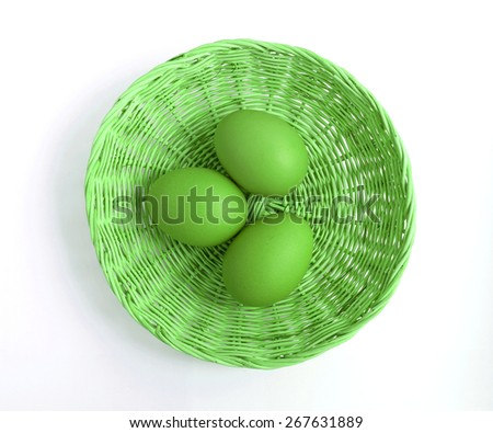 Green eggs in basket from top view - stock photo