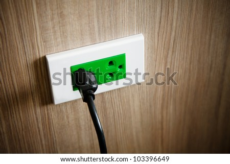Green electrical outlet on a wood wall. - stock photo