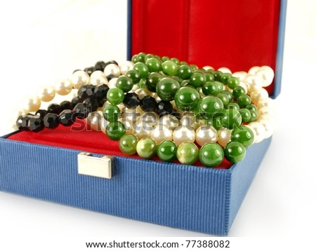 Green emerald gemstone necklace over white and black pearls, in a jewlry box, isolated towards white - stock photo