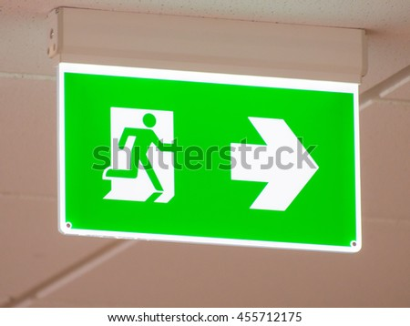 Green emergency exit light sign in the office