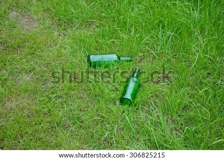 Green empty beer bottles on the lawn