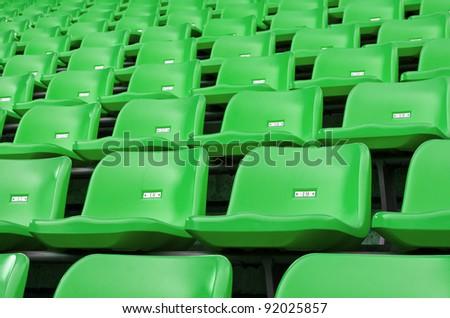 Green Empty plastic seats at stadium open door sports arena - stock photo