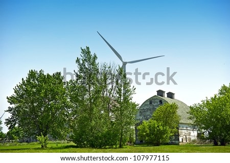Green Energy and Old Farm Barn Between Threes. Modern Wind Turbine in Background. - stock photo
