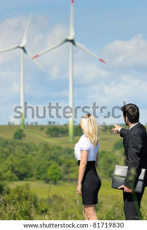 Green energy businesspeople - Young businesswoman pointing at windmill in field