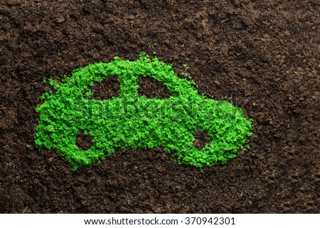 Green energy car concept with grass in shape of a car - stock photo