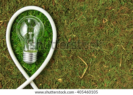 Green energy. Concept ecology. Light bulb on green natural moss with copy space - stock photo