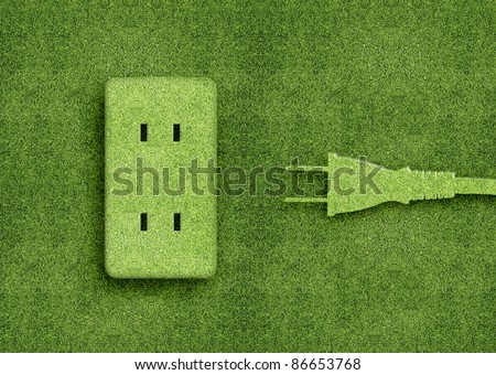 Green energy concept, Green power cord in electric outlet on a green grassland.