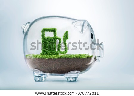 Green energy concept with grass growing in shape of fuel pump inside transparent piggy bank - stock photo