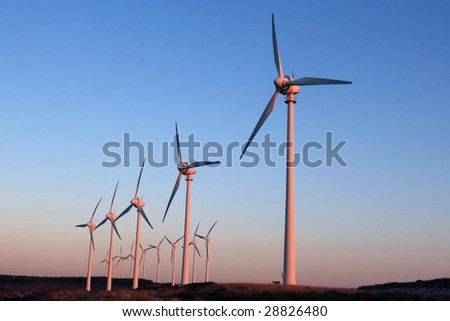 green energy producer windfarm at the sunset - stock photo