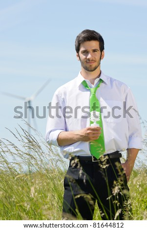 Green energy - young businessman hold light bulb in windmill field - stock photo
