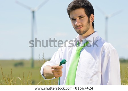 Green energy - young businessman hold plug in field with windmill - stock photo