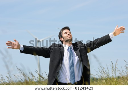Green energy - Young businessman in field windmill in background - stock photo