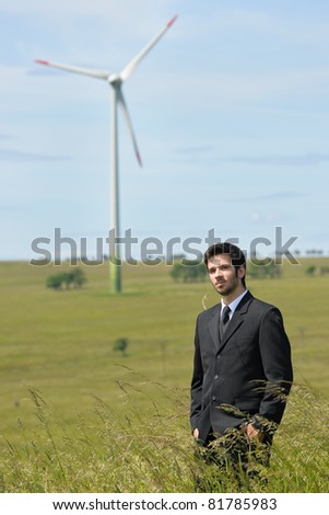 Green energy - Young businessman in field windmill in background