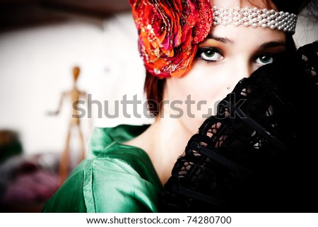 green eye woman with black fan and pearl and rose headband - stock photo