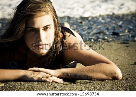 Green eyed beauty laying over the sand - stock photo