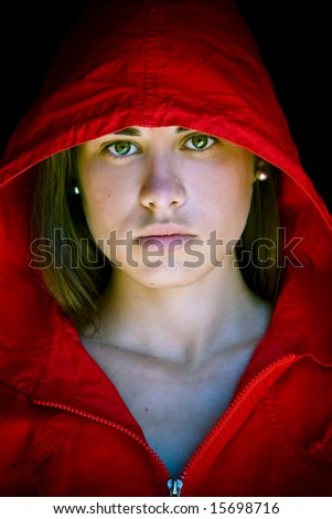 Green eyed beauty protected with a red cap from the dark. - stock photo