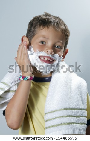 Green-eyed blond child with yellow flannel is smiling while placing shaving cream in the face - stock photo