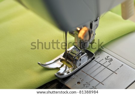 Green fabric on a sewing machine - stock photo