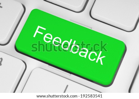 Green feedback button on keyboard close-up - stock photo