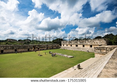Green field and beautiful mayan ruins of Ushmal in Mexico under the cloudy sky - stock photo
