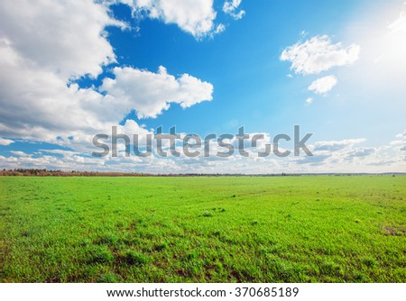 green field and blue cloudy sky - stock photo