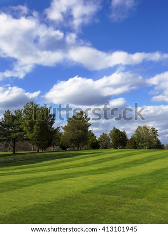 Green field and blue sky. Spring background. Open golf course field. Puffy clouds with trees and green field