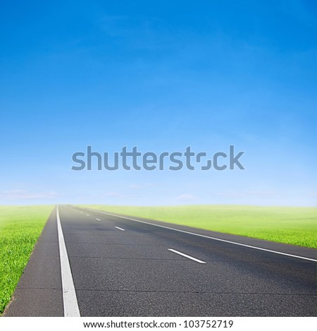 green field and car road over blue sky - speed and travel - stock photo
