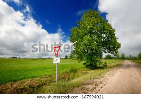 Green field and the road sign on a country road against stormy sky - stock photo